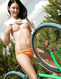 Hot teenage cutie on a bike plays with a big toy